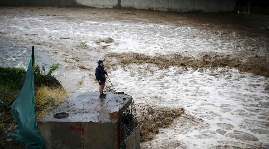 A man is seen next to a river during floods in Santiago, April 17, 2016. © Ivan Alvarado