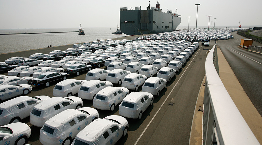 New cars of several brands of German carmaker Volkswagen AG are covered with protective covers before they are loaded for export on a transport ship at the harbour of the Volkswagen plant in Emden © Christian Charisius
