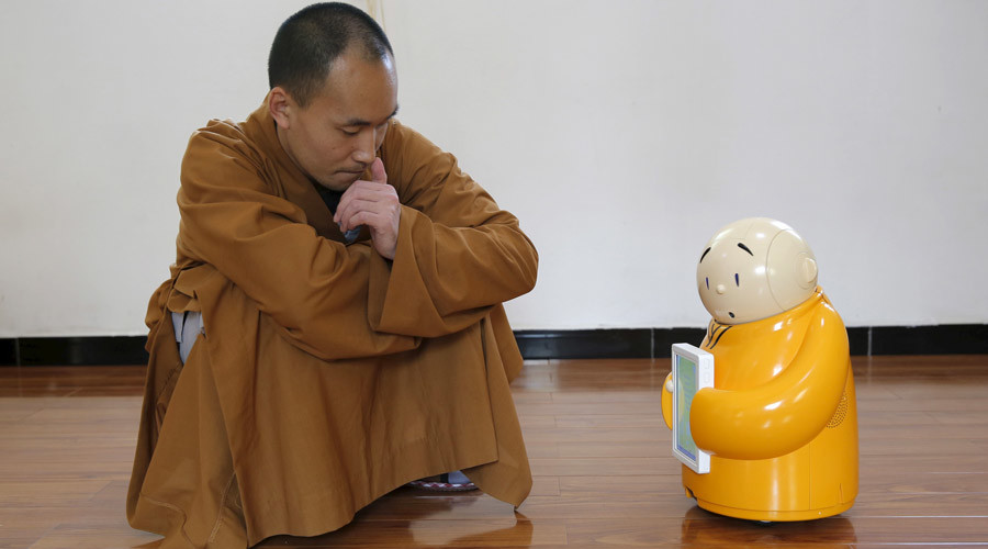 Master Xianfan looks at robot monk Xian'er as he demonstrates the robot's conversation function during a photo opportunity in Longquan Buddhist temple on the outskirts of Beijing, April 20, 2016. © Kim Kyung-Hoon