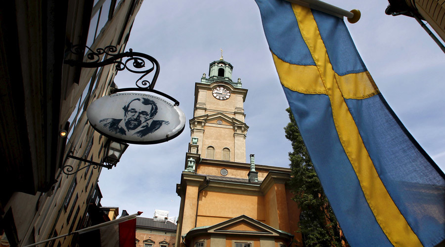 Sweden's flag waves near the Stockholm Cathedral in Gamla Stan or the Old Town district of Stockholm, Sweden © Bob Strong