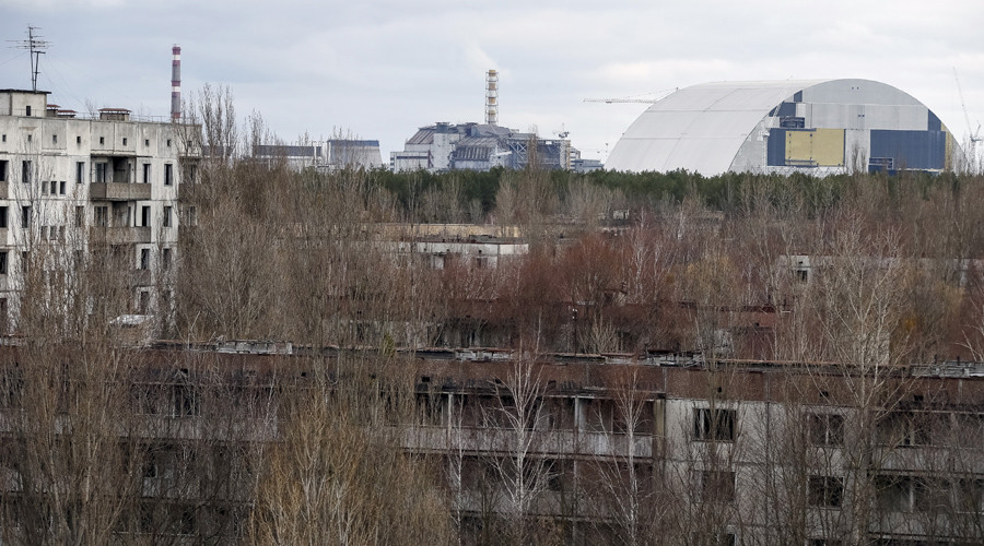 A containment shelter for the damaged fourth reactor (L) and the New Safe Confinement (NSC) structure (R) at the Chernobyl Nuclear Power Plant are seen from Ukraine's abandoned town of Pripyat, Ukraine, March 23, 2016. © Gleb Garanich