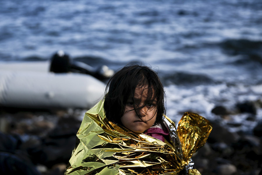A migrant girl covers herself with a thermal blanket after arriving on a raft on the Greek island of Lesbos © Alkis Konstantinidis