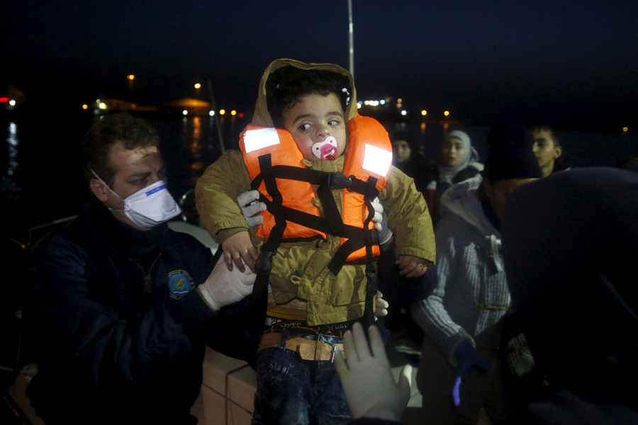 A Coast Guard officer hands over a child to a fellow colleague as refugees and migrants disembark a Greek Coast Guard vessel at the port of Mytilene on the Greek island of Lesbos © Giorgos Moutafis