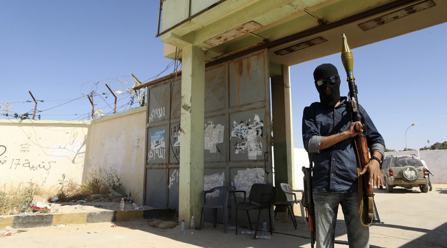 A militia stands guard in front of the entrance to the February 17 militia camp after Libyan irregular forces clashed with them in the eastern city of Benghazi. © Esam Al-Fetori
