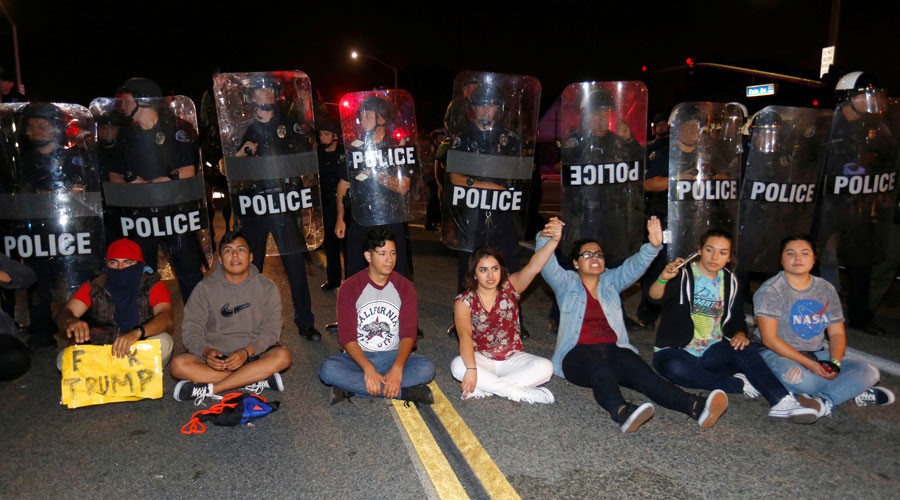 Demonstrators sit in front of a line of police in riot gear outside Republican U.S. presidential candidate Donald Trump's campaign rally in Costa Mesa, California April 28, 2016. © Mike Blake