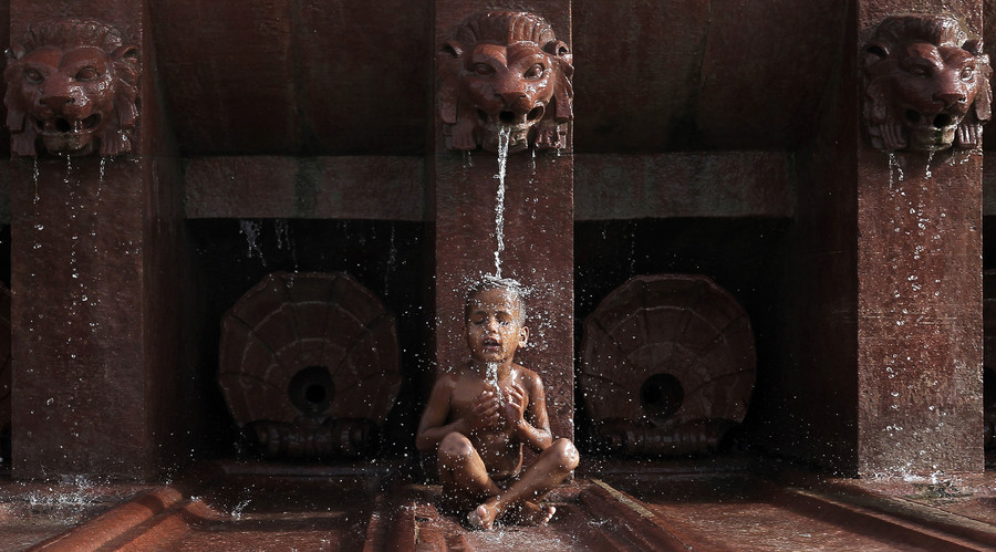 A boy cools himself off as he sits under a fountain on a hot summer day in New Delhi. © Adnan Abidi