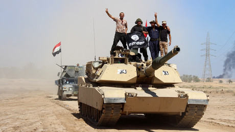 Members of Iraqi government forces celebrate on a tank with a seized flag of the Islamic State group (IS) after they retook an area from its jihadists on April 2, 2016 in the village of Al-Mamoura, near Heet in the western province of Anbar. © Moadh Al-Dulaimi