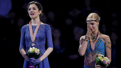 Gold medalist Evgenia Medvedeva of Russia (L) and bronze medalist Anna Pogorilaya of Russia react during their national anthem on the awards podium.  © Brian Snyder