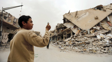A boy takes a picture with his mobile phone of damaged buildings during his visit to the city of Palmyra, Syria April 9, 2016. © Omar Sanadiki