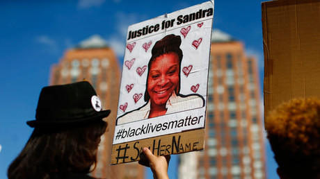 A woman holds a poster bearing the portrait of Sandra Bland, a 28-year-old black woman who killed herself in a Texas jail cell in 2015. © Kena Betancur