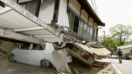 A man walks near a damaged house and car caused by an earthquake in Mashiki town, Kumamoto prefecture, southern Japan, in this photo taken by Kyodo April 15, 2016. © Kyodo