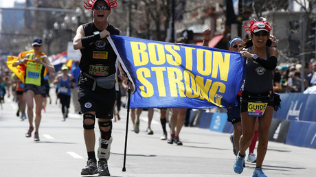 Bryon Solberg is helped by a guide and reacts while finishing the 120th Boston Marathon. © Greg M. Cooper