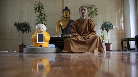 Master Xianfan sits next to robot Xian'er as he poses for photograph at Longquan Buddhist temple on the outskirts of Beijing, April 20, 2016.  © Kim Kyung-Hoon