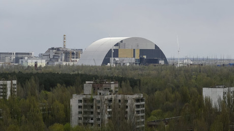 A containment shelter for the damaged fourth reactor (L) and the New Safe Confinement (NSC) structure (R) at the Chernobyl Nuclear Power Plant are seen from Ukraine's abandoned town of Pripyat, Ukraine, April 22, 2016.  © Gleb Garanich