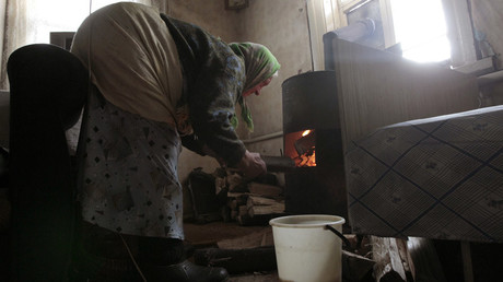 Pensioner puts firewood into her cast-iron moveable wood stove © Vasily Fedosenko
