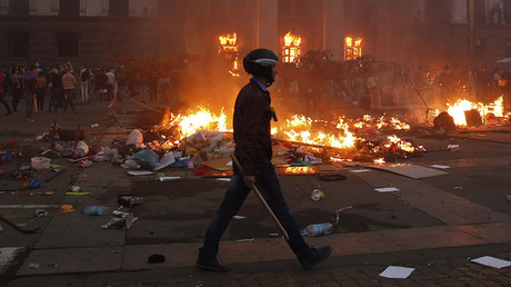 A protester walks past a burning tent camp and a fire in the trade union building in Odessa May 2, 2014. © Yevgeny Volokin