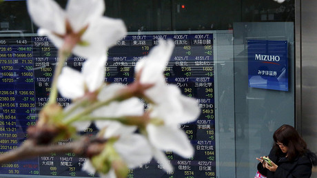 A woman uses a smart phone next to an electronic stock quotation board, as cherry blossoms bloom, outside a brokerage in Tokyo, Japan © Issei Kato