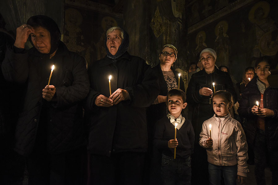 Serbian Orthodox believers hold candles during Orthodox Easter religious services in the Medieval Monastery in the town of Gracanica on April 30, 2016. © Armend Nimani
