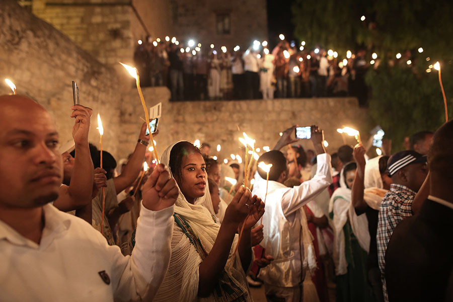 "Ethiopian Christian pilgrims hold candles during an Ethiopian Orthodox ceremony of the ""Holy Fire"" at the Dir Al-Sultan Church held on the roof of the Holy Sepulcher in Jerusalem's Old City on April 30, 2016. © AFP"