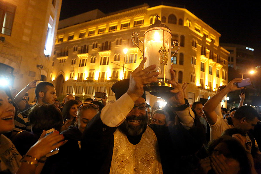 A Greek Orthodox Christian priest holds the Holy Fire as he arrives in downtown Beirut from Jerusalem through Amman on April 30, 2016. ©Patrick Baz