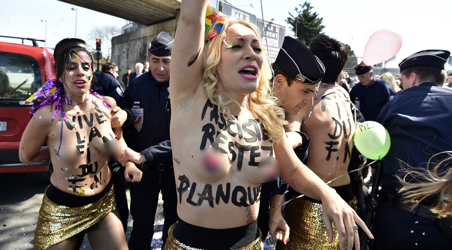 Inna Shevchenko (C) and other topless Femen activists protest outside a banquet held by France's far-right Front National (FN) party in honour of Jeanne d'Arc (Joan of Arc) at the Porte de La Villette in Paris on May 1, 2016. 