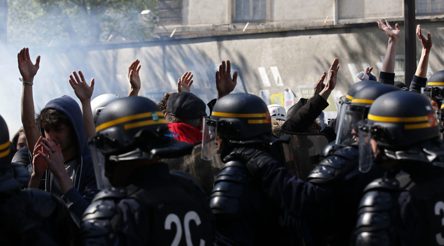 Youths raise their hands high to show that they do not hold bottles or stones as they pass French riot police during a protest against the French labour law proposal during the May Day labour union march in Paris, France, May 1, 2016. © Philippe Wojazer