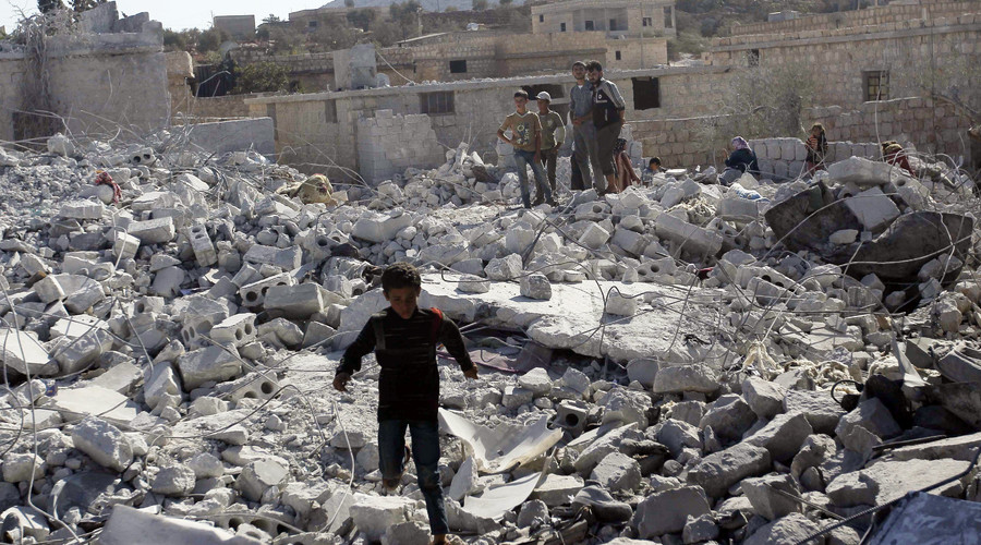Residents inspect damaged buildings after a U.S. strike, in Kfredrian, Idlib province September 23, 2014. © Abdalghne Karoof