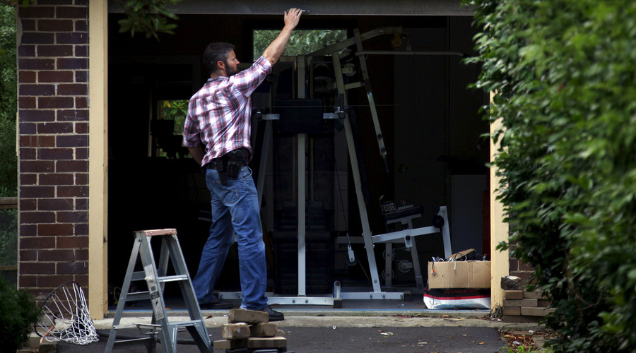 An Australian Federal Police officer closes the door of the garage after searching the home of probable creator of cryptocurrency bitcoin Craig Steven Wright in Sydney's north shore December 9, 2015. © David Gray
