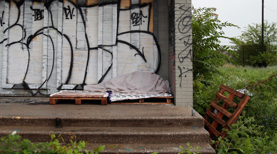 A homeless person sleeps under a blanket on the porch of a shuttered public school covered with graffiti in a once vibrant southwest neighborhood in Detroit © Rebecca Cook