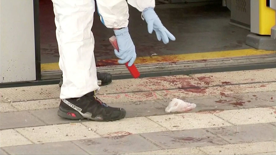 An police investigator looks at bloodstained footprints leading out of a train and on a platform following a knife attack in Grafing train station, south east of Munich, Germany, in this still image taken from video May 10, 2016. © Reuters TV