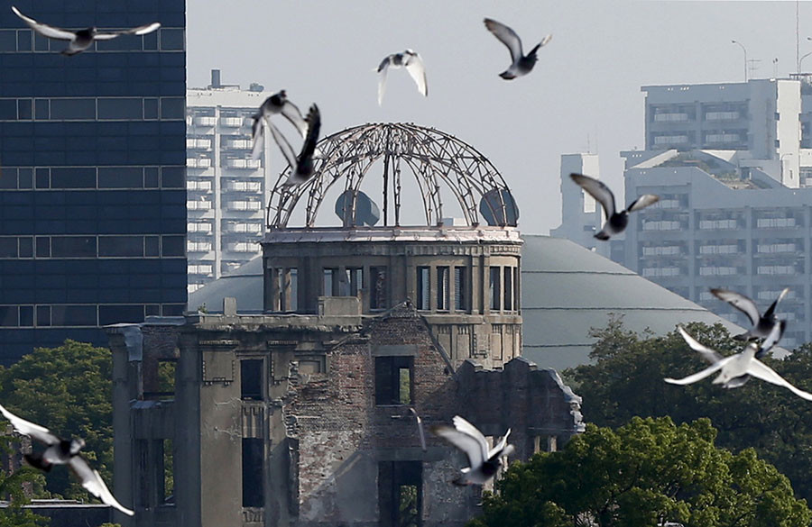 Doves fly over Peace Memorial Park with Atomic Bomb Dome in the background, at a ceremony in Hiroshima, western Japan, August 6, 2015, on the 70th anniversary of the atomic bombing of the city. © Toru Hanai