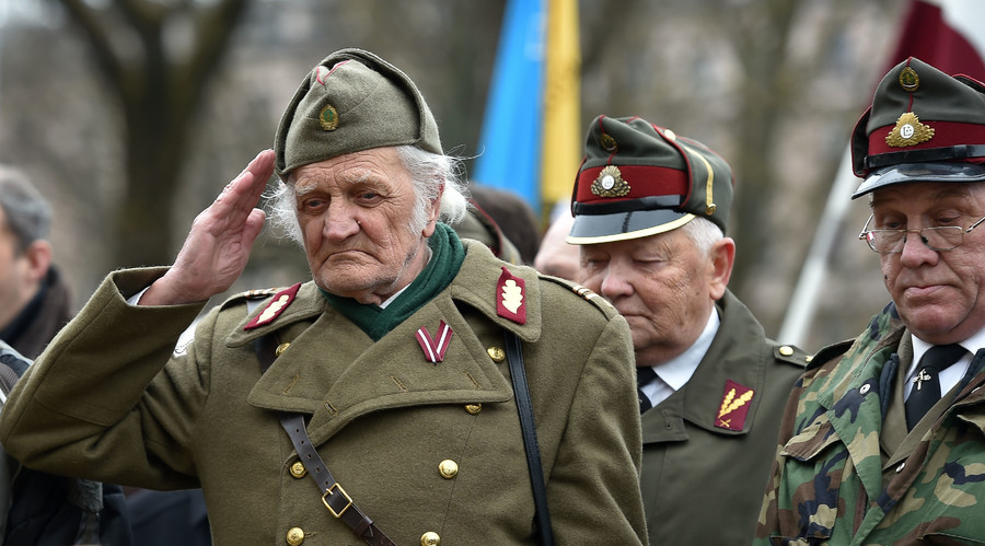 A man dressed in a pre-WWII Latvian military uniform salutes as veterans of the Latvian Legion walk to the Monument of Freedom in Riga, Latvia on March 16, 2016. © Ilmars Znotins