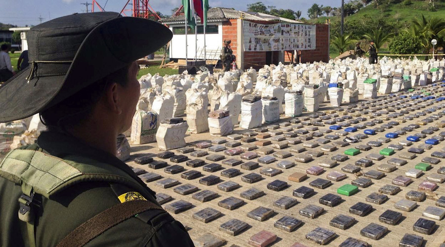 A Colombian police officer standing guard over eight tons of seized cocaine in Turbo, Antioquia department, on May 15, 2016. © Colombian police
