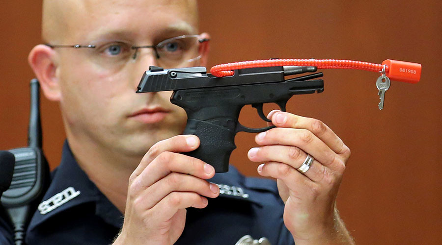 Sanford police officer Timothy Smith holds up the gun that was used to kill Trayvon Martin, while testifying during George Zimmerman's murder trial in Seminole circuit court in Sanford, Florida, June 28, 2013. © Joe Burbank