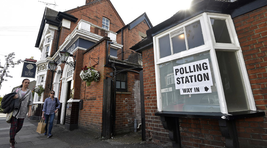 People walk past a pub being used as a polling station in west London © Toby Melville