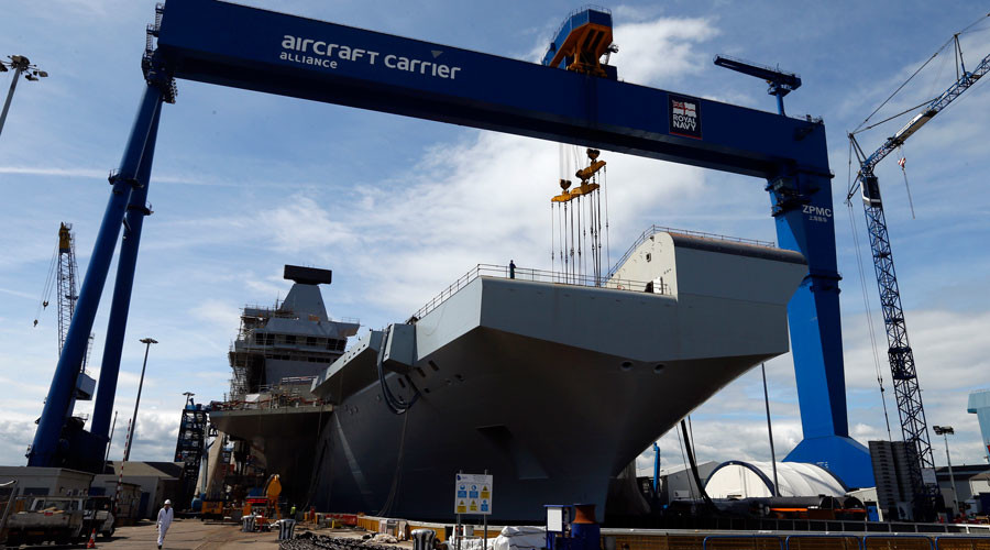 Workers walk in front of HMS Queen Elizabeth, the first of two aircraft carriers being built by British defence firm BAE Systems, at Rosyth dockyard in Fife, Scotland © Russell Cheyne