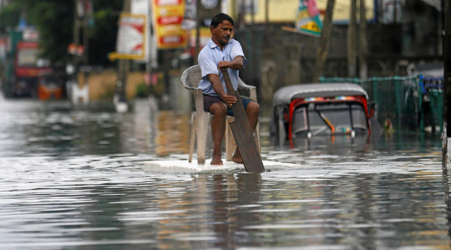 A man sits on a chair as he uses a piece of styrofoam to move through a flooded road in Wellampitiya, Sri Lanka May 21, 2016 © Dinuka Liyanawatte