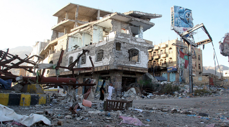 People walk past a building destroyed during recent fighting in Yemen's southwestern city of Taiz © Anees Mahyoub