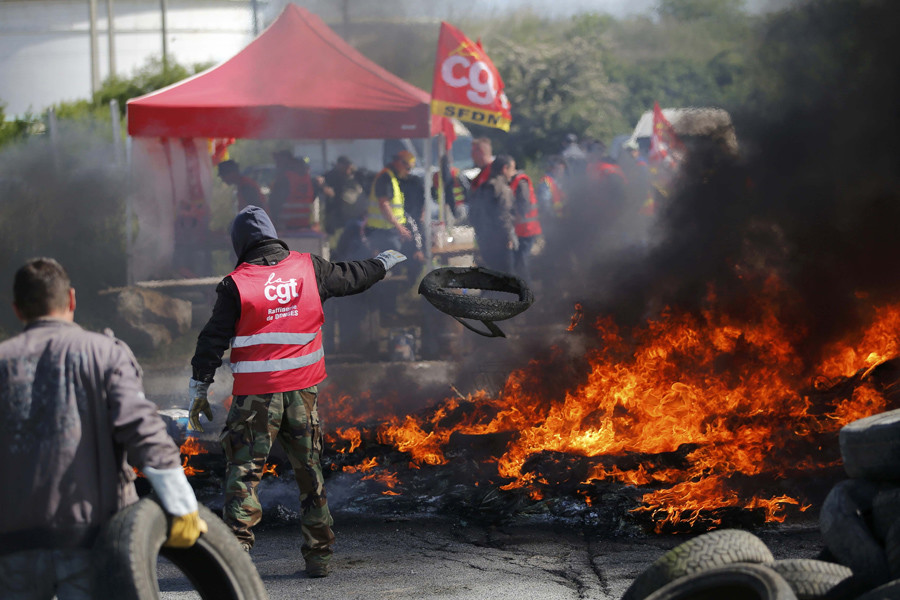 A French CGT labour union employee at French oil giant Total throws a tyre onto a burning barricade to block the entrance of the depot of the SFDM company near the oil refinery of Donges, France, May 19, 2016. © Stephane Mahe