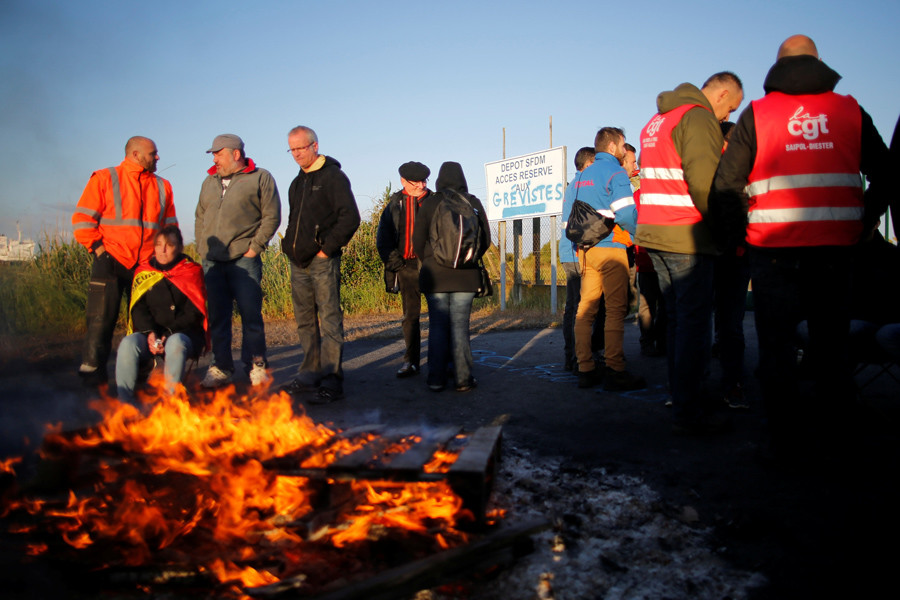 French workers and protesters walk near a barricade to block the entrance of the fuel depot of the society SFDM near the oil refinery of Donges, France, May 23, 2016. © Stephane Mahe
