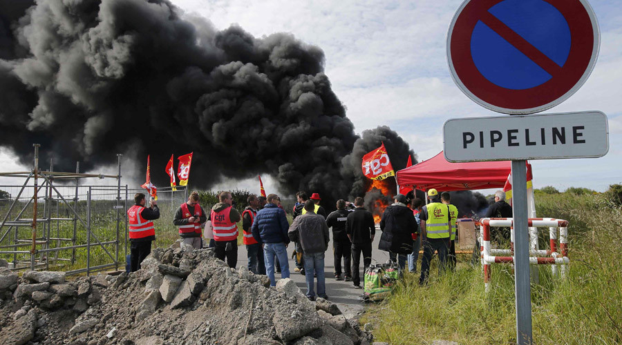 Labour union employees at French oil giant Total stand near a burning barricade to block the entrance of the deposit of the society SFDM near the oil refinery of Donges, France, May 19, 2016. © Stephane Mahe