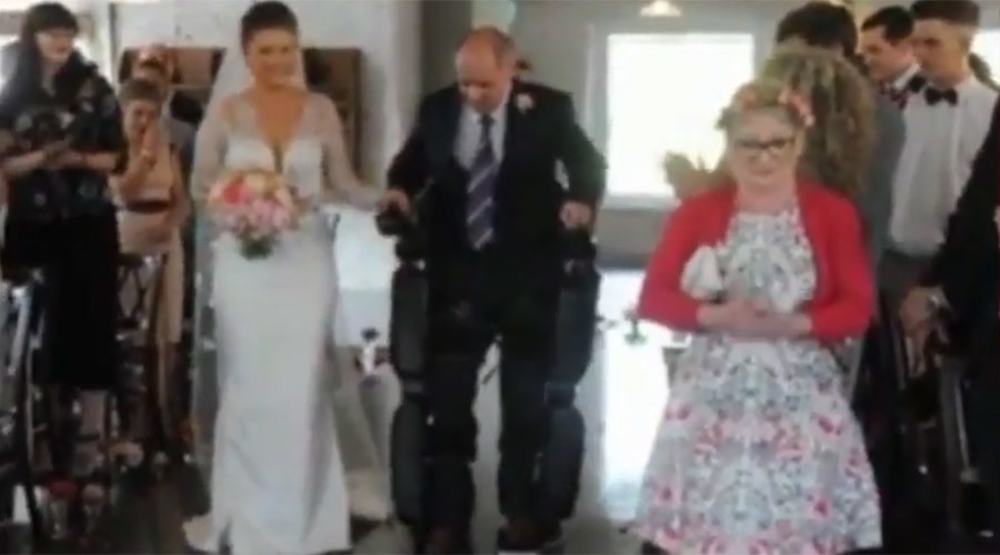 Paralyzed dad dons robot suit to walk daughter down the aisle (VIDEO)