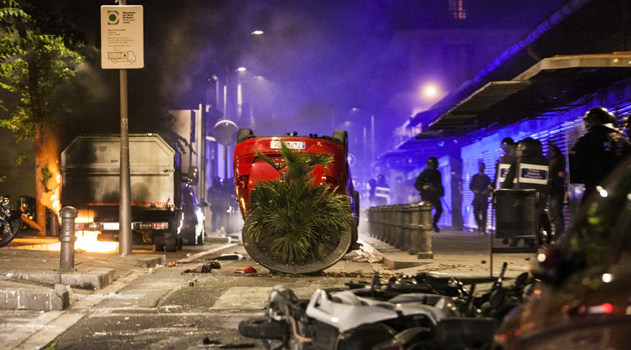 A truck burns next to overturned cars and motorcycles during riots after a demonstration against the evacuation of an occupied old bank branch in Barcelona, on May 23, 2016. © AFP