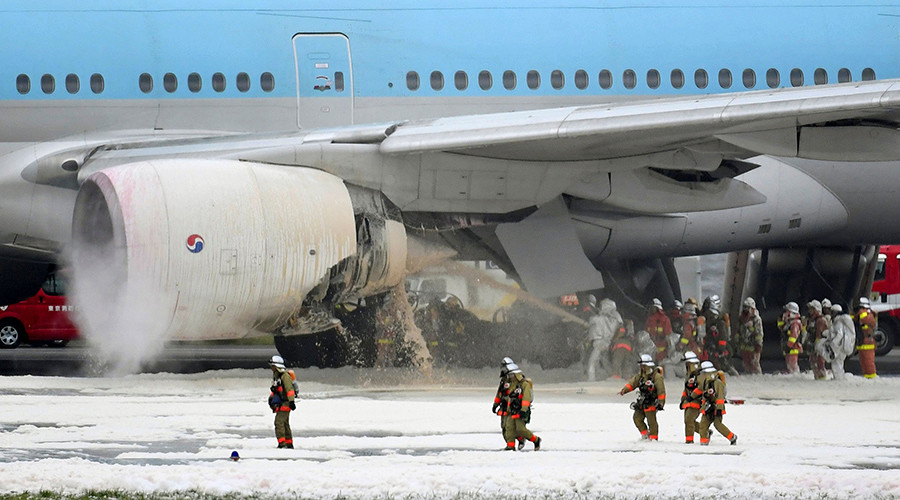 Firefighters spray foam at the engine of a Korean Air Lines plane after smoke rose from it at Haneda airport in Tokyo, Japan, May 27, 2016 © Kyodo