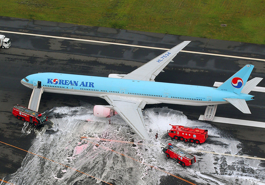 An aerial picture shows passengers standing near a Korean Air Lines plane after smoke rose from one of its engines at Haneda airport in Tokyo, Japan, May 27, 2016 © Kyodo