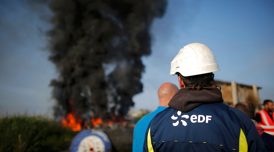 A striking French labour union EDF employee stands near a burning barricade that blocks the entrance of the depot of the SFDM company near the oil refinery to protest the labour reforms law proposal in Donges, France, May 27, 2016 © Stephane Mahe