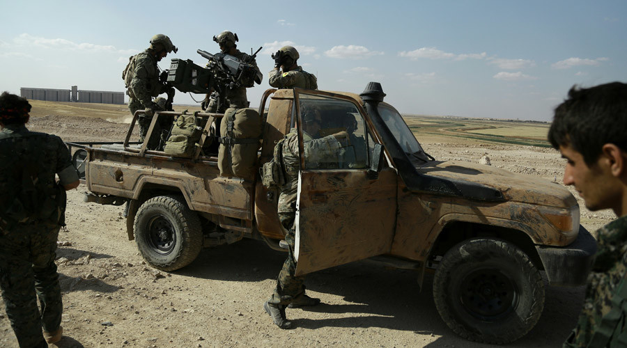 Armed men in uniforms identified by Syrian Democratic forces as US special operations forces stand in the back of a pickup truck in the village of Fatisah in the northern Syrian province of Raqa on May 25, 2016. © Delil Souleiman