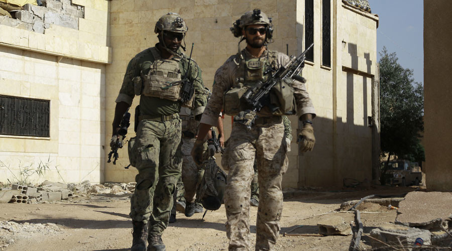 Armed men in uniform identified by Syrian Democratic forces as US special operations forces walk in the village of Fatisah in the northern Syrian province of Raqa on May 25, 2016. © Delil Souleiman