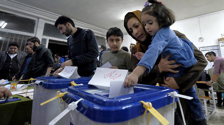 An Iranian woman holding her daughter casts her ballot during elections  in Tehran  © Raheb Homavandi