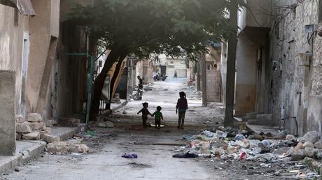 Children walk near garbage in al-Jazmati neighbourhood of Aleppo, Syria April 22, 2016. © Abdalrhman Ismail